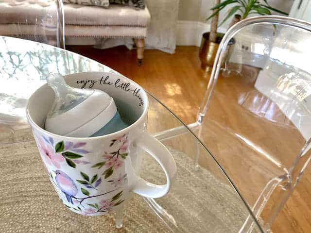 warming a baby milk bottle in a mug