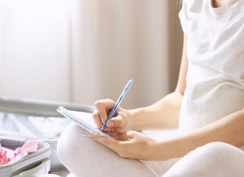 pregnant woman writing hospital bag checklist