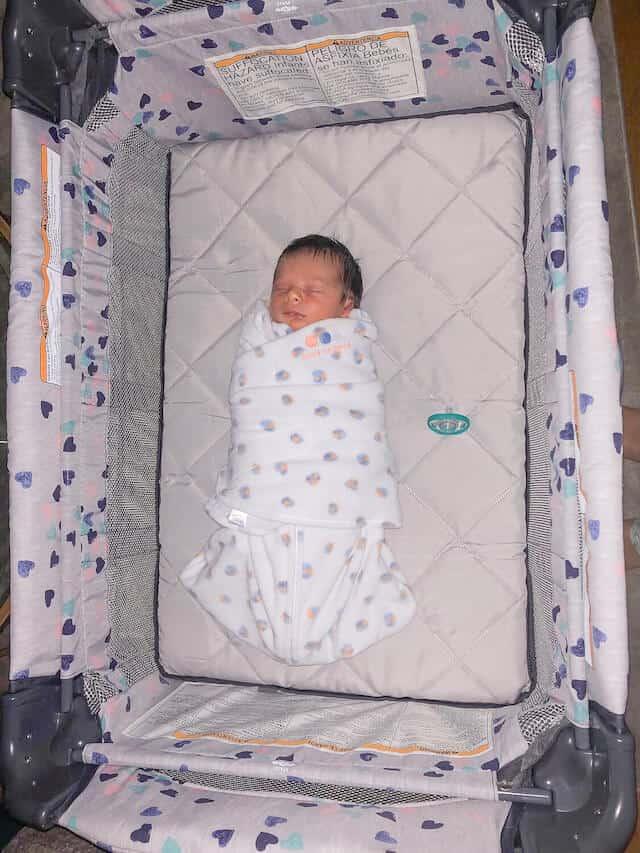 swaddled newborn baby sleeping pack n play
