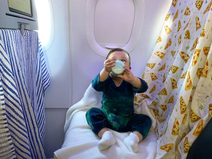 baby on plane with blankets covering seat