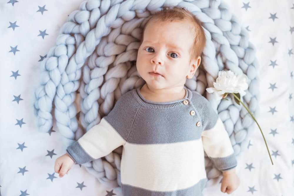 baby boy lying on knit blanket