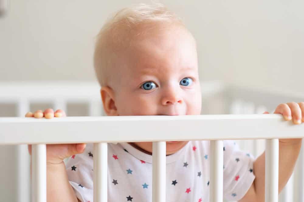 baby biting crib rail