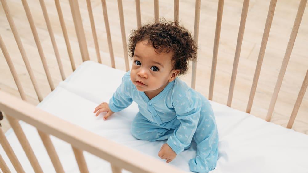 baby sitting in safe crib