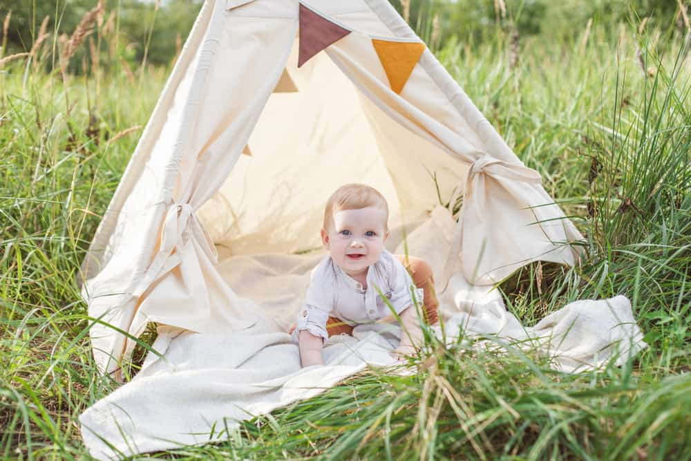 One year cute boy in a teepee outdoors