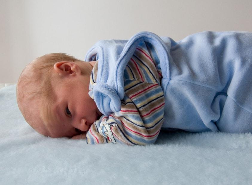 newborn baby rolling on belly